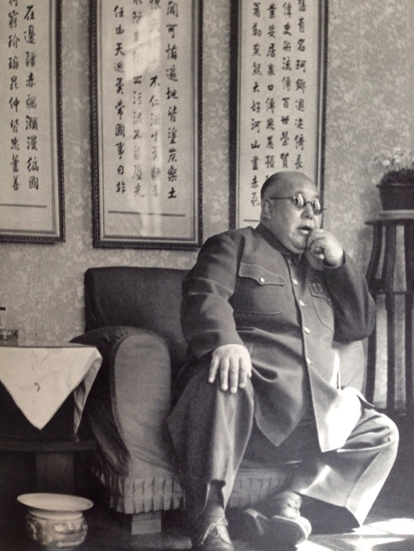 "General Ma Hung-kwei came to Nanking, Kuomintang capital, every year to meet Marshal Chiang K'ai-shek.  The first syllable of his name, Ma, means horse, a very common name designation among Chinese Moslems.  Behind him, carefully written, are some old ryhmed precepts: ""A good general should occupy a splendid place in history.  He should be praised during a hundred generations.  He should be full of care for his men and also for his people.""  General Ma was the big war lord of Northwest China.  His secretaries were dressed as hospital nurses.  He adored ice cream and always had bucketfuls handy, and offered to his guests.  Shortly after this photograph was taken, General Ma was abandoned by his troops."