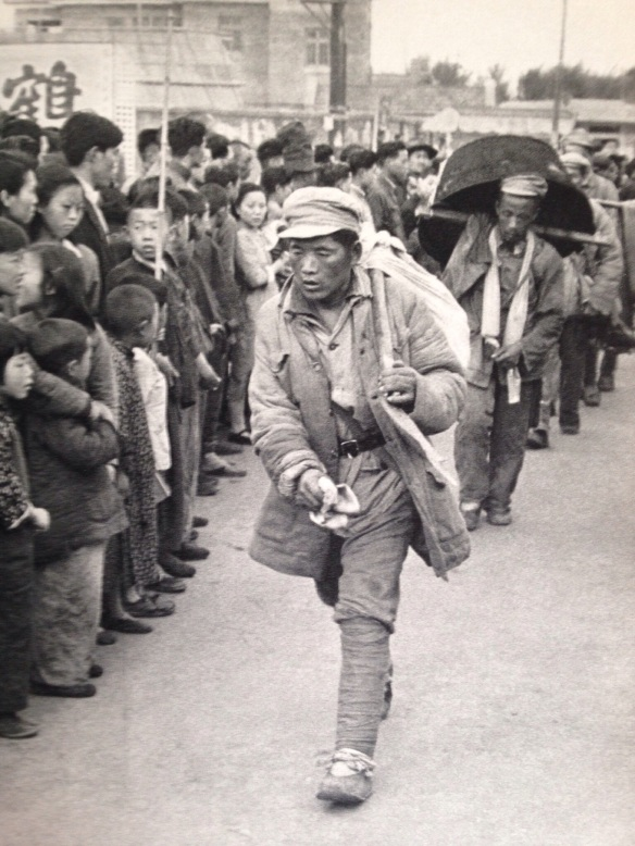 The first soldiers arriving in Nanking on foot.  They are cheered, but at the same time regarded with good deal of anxious curiosity.  In China, a soldier has always been considered a looter, living off the country, for which reason the military profession is greatly despised.