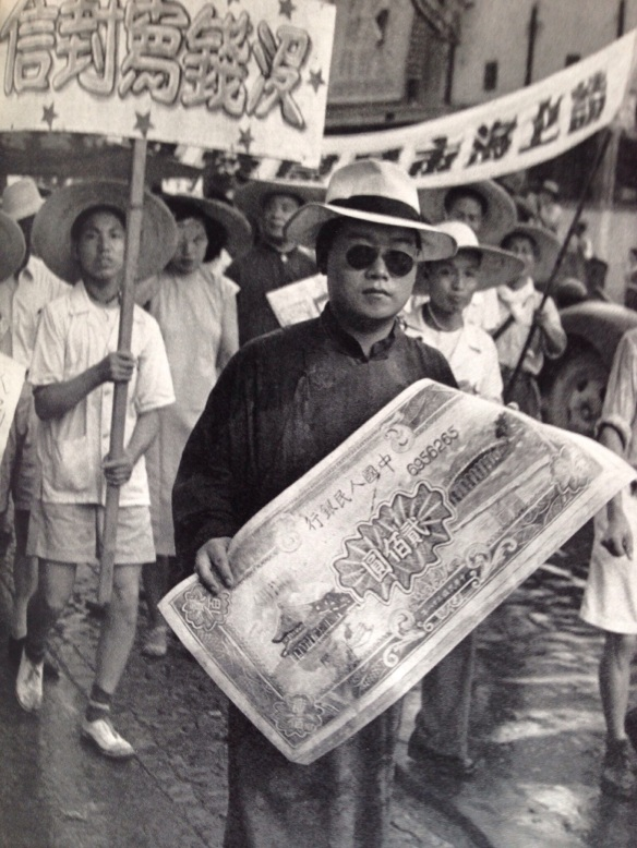 After the taking of Shanghai there were so many parades and meetings that they almost overlapped.  Here is the celebration of the official entry of the army into Shanghai on August 1, 1949.  A Union delegate holds an enlarged copy of the new paper money.  The processions were used to publicize the problems of the hour.  The ceremony had been planned for July 5 but in the face of the Kuomintang threat to bomb it from the air, it was postponed to the 6th.